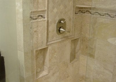 Reworked standard shower into custom tile shower with custom shower enclosure and built in niches.