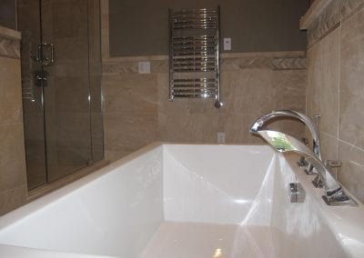 close up look of the tub area and faucet looking towards the wall hung towel warmer