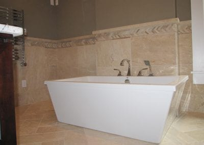Step out of this freestanding soaking tub onto a heated floor.