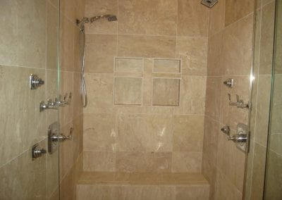 master shower area with bench. Both sides have their own shower set up.