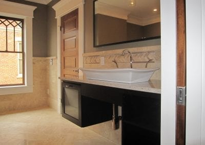 Wall hung cabinets allow for a clean look. The beautiful tile flows through-out this grand master ba