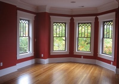wood window with white trim and refinished floors